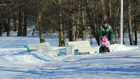 Ein Mann sledging seine Tochter stock video