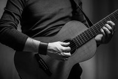 Ein Mann spielt auf akustischer Wohnzimmergitarre Lizenzfreie Stockfotografie