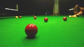 Ein Mann spielt Billard Helle bunte Bälle, zum des Snookers zu spielen Gedämpfte Lichter Stockfoto