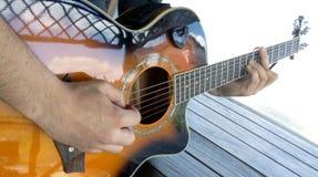 Ein Mann spielt eine Akustikgitarre mit zwei Handnahaufnahmebild Lizenzfreie Stockfotografie