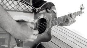 Ein Mann spielt eine Akustikgitarre mit zwei Handnahaufnahmebild b Lizenzfreie Stockfotografie