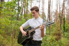 Ein Mann spielt eine Gitarre im Freien Stockbilder