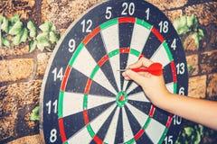 Ein Mann spielt Pfeile und hält den Pfeil mit seiner Hand, um das Ziel auf dem Ziel zu schlagen stockfoto