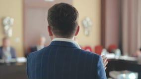 Ein Mann spricht öffentlich mit Kollegen und Aktien seine Erfahrung in der Finanzierung und im Geschäft stock footage