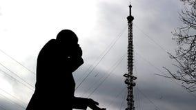 Ein Mann spricht emotional am Telefon vor dem hintergrund eines Telefonturms, wellenartig bewegt seine Hände stock video