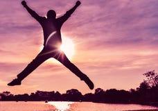 Ein Mann springt in die Luft, er ist sehr glücklich im Leben mit Sonne stockfoto