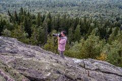 Ein Mann steht auf einem Felsen und Trieb Stockfotografie