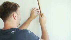 Ein Mann steht die Wand bereit und hämmert einen Nagel mit einem Hammer stock video footage