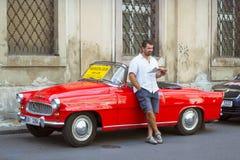 Ein Mann steht an einem hellen roten Retro- Auto Skoda Lizenzfreies Stockbild