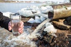 Ein Mann steht mit einem Glas, das mit Wasser vom Abwasserkanal gefüllt wird Lizenzfreie Stockfotos
