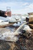 Ein Mann steht mit einem Glas, das mit Wasser vom Abwasserkanal gefüllt wird Stockbild