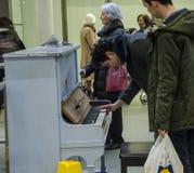 Ein Mann stoppt, um auf einem alten Klavier in internationalem Bahnhof St Pancras zu spielen Lizenzfreie Stockfotografie