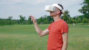 Ein Mann trägt den Rahmen ein, setzt einen VR-Kopfhörer auf seinen Kopf in einen Park und in Anfänge mit ihm ein stock video footage