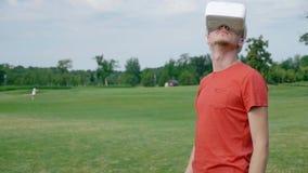 Ein Mann trägt den Rahmen ein, setzt an seinen Kopf ein VR-Kopfhörer in den Park ein und schaut herum stock footage