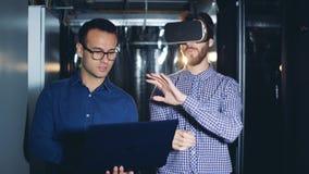 Ein Mann trägt VR-Gläser in einem Serverraum, Abschluss oben stock footage