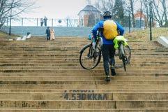 Ein Mann trägt zwei Fahrräder herauf die Treppe, Treppe oben vom Meer stockfotos