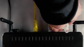 Ein Mann trennt das Ethernet-Kabel von den WAN- und LAN-Häfen des WiFi-Routers nahaufnahme stock footage