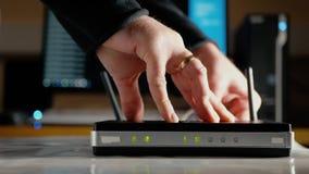Ein Mann trennt die Ethernet-Kabel vom WAN-Hafen und VON LAN-Häfen des WiFi-Routers stock video