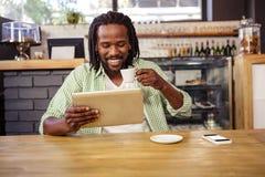 Ein Mann trinkt einen Tasse Kaffee, während seine Tablette schaut stockfotografie
