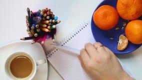 Ein Mann trinkt Kaffee von einer Schale auf dem Tisch Dann nimmt er einen Stift und denkt an was, in ein Notizbuch zu schreiben G stock video