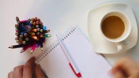 Ein Mann trinkt Kaffee von einer Schale auf dem Tisch Dann nimmt er einen Stift und denkt an was, in ein Notizbuch zu schreiben G stock video footage