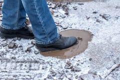 Ein Mann tritt in eine gefrorene Pfütze mit Schlamm Stockbild