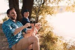 Ein Mann und ein alter Mann auf der Flussbank Der Mann lacht und bereitet vor sich, die Fische auszuziehen, der alte Mann fischt  Lizenzfreie Stockfotografie