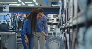 Ein Mann und eine Frau, die Tür der Waschmaschine zu öffnen kontrollieren den Entwurf und die Qualität, bevor sie im Speicher  stock video footage
