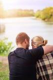 Ein Mann und eine Frau in einer Wolldecke sitzen die Umfassung auf der Flussbank Umarmungen eines liebevolle Paares in einer Woll Stockfotos