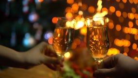Ein Mann und eine Frau heben Gläser funkelnden Champagner über einer festlichen Tabelle an stock video