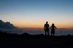 Ein Mann und eine Frau im Schattenbild, das in Richtung zum Horizont der untergehenden Sonne über dem Mittelmeer betrachtet Lizenzfreie Stockfotos
