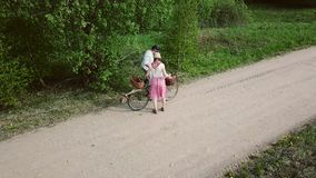 Ein Mann und eine Frau mit einem Fahrrad und Körbe gehen entlang die Straße stock footage