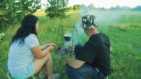 Ein Mann und eine Frau sitzen durch das Feuer, über dem der Werfer hängt der Mann mischt die Kohlen im Feuer stock footage