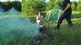 Ein Mann und eine Frau sitzen durch das Lagerfeuer nahe dem Zelt und dem trinkenden Tee stock video footage