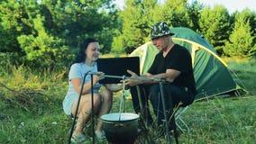 Ein Mann und eine Frau sitzen an einem Zelt und passen einen Werfer, über einem Feuer zu hängen auf und mit einem Laptop zu arbei stock footage