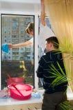 Ein Mann und eine Frau waschen ein Fenster Stockfotografie