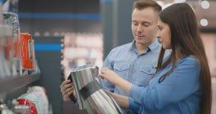 Ein Mann- und Frauengriff in ihren Händen ein Wasserkocher in einem Speicher, der bevor dem Kaufen im Gerätespeicher wählt stock video footage