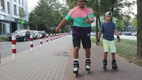 Ein Mann und ein Junge reiten Rollschuhe im Park stock video footage