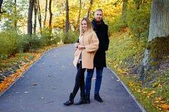 Ein Mann und seine Freundin, die auf der Straße in einem Herbst aufwerfen, parken Stockfotografie