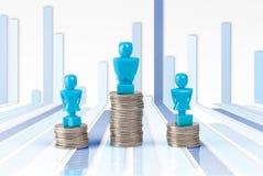 Ein Mann und zwei Frauenstatuetten, die auf Stapel von Münzen stehen Stockbild