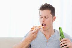 Ein Mann ungefähr, zum von etwas Pizza zu essen, wie er etwas Bier hält Lizenzfreie Stockfotos
