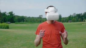 Ein Mann unter Verwendung eines VR-Kopfhörers im Park und in den ausweichen Hindernissen stock video footage