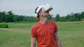 Ein Mann unter Verwendung eines VR-Kopfhörers im Park und in den Drehungen sein Kopf oben stock video