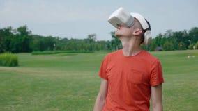 Ein Mann unter Verwendung eines VR-Kopfhörers im Park und in den Drehungen sein Kopf oben stock video footage