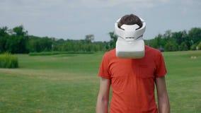 Ein Mann unter Verwendung eines VR-Kopfhörers im Park und in den Drehungen sein Kopf unten stock video footage