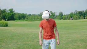 Ein Mann unter Verwendung eines VR Kopfhörers und Spielens eines virtuellen Spiels im Park stock video footage