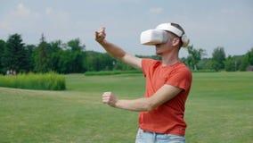 Ein Mann unter Verwendung eines VR Kopfhörers und Spielens eines virtuellen Spiels im Park stock footage