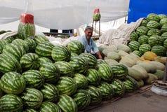 Ein Mann verkauft Melonen und Wassermelonen Stockfotografie