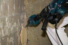 Ein Mann verpackt Fliesen mit einem Demolierungshammer Stockbild