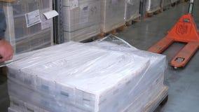 Ein Mann verpackt Produkte mit Zellophan in einem logistischen Lager 4K langsames MO stock video footage